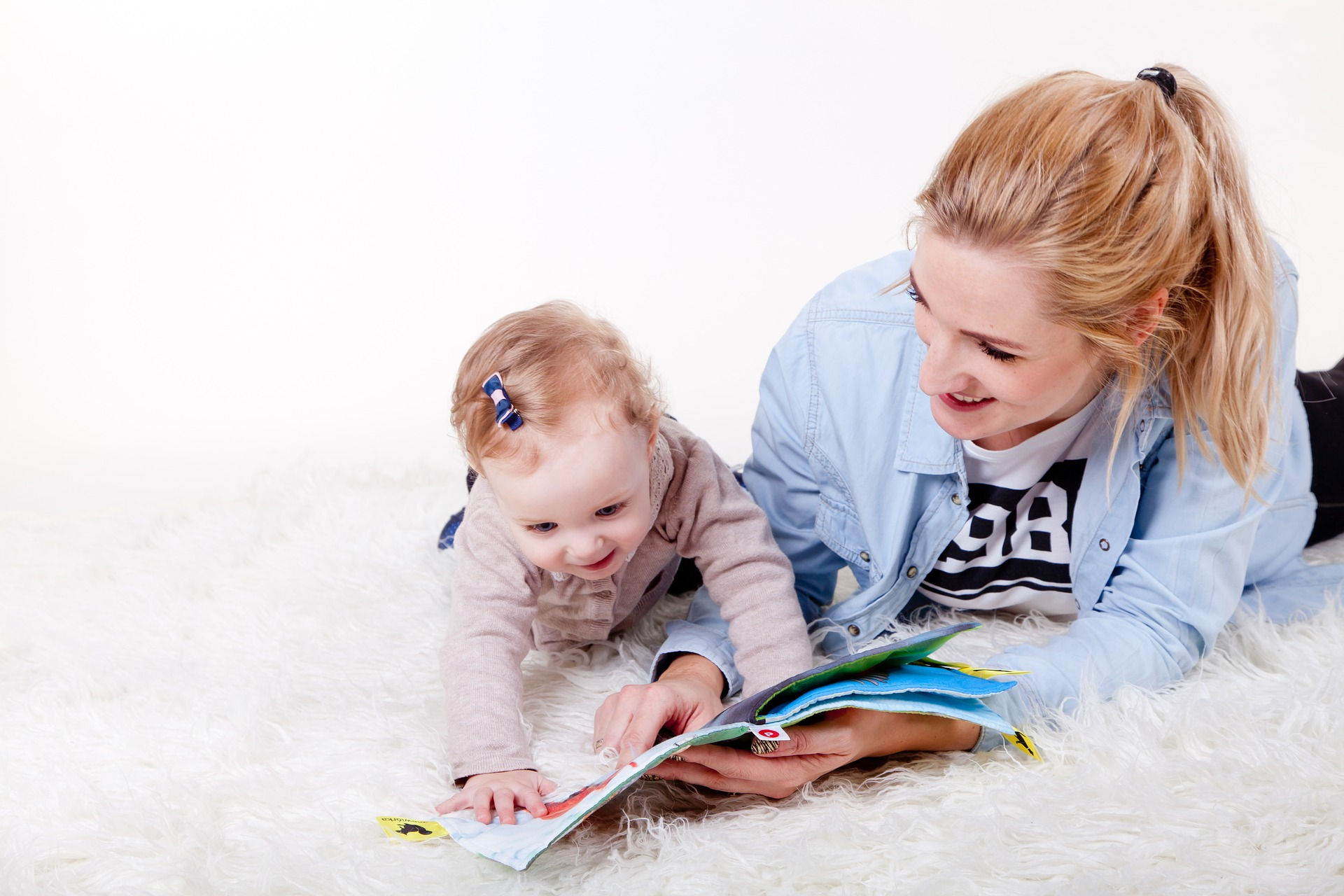 Mother and young baby looking at book together