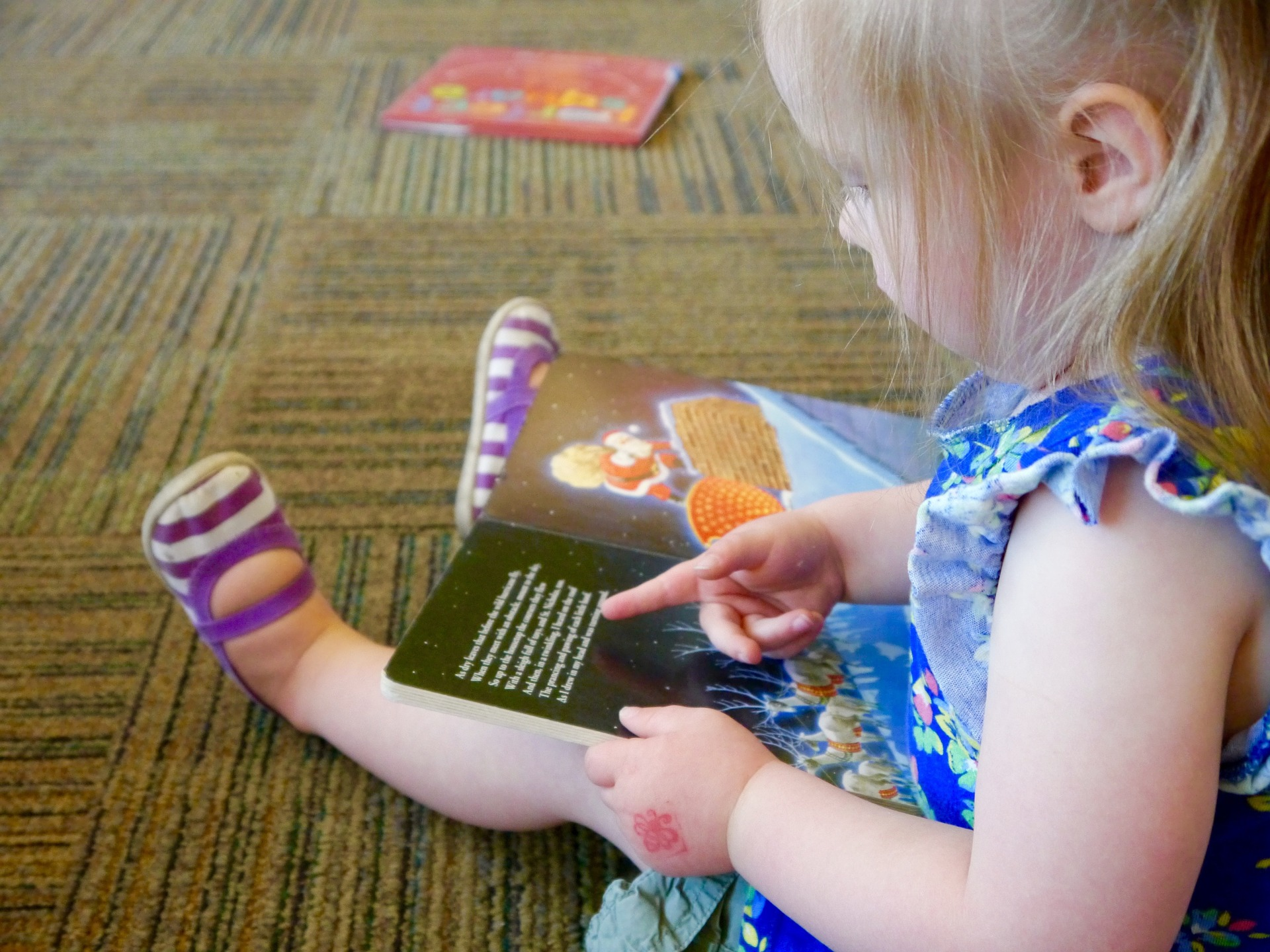 Toddler girl sitting in the library with open picture book on lap